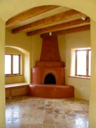 Kiva fireplace in livingroom with recessed daybed on the left.