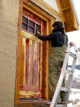 A friend installing a homemade door in his lovely Tiny home. Llama, NM.
