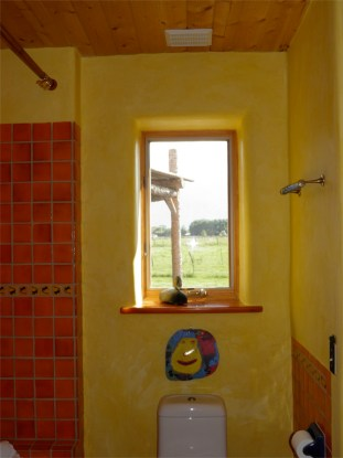 Window in straw bale wall with hand dyed plaster.