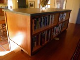Custom built cabinet with a green SileStone counter serves as a bookcase for the den.