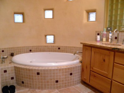 Oval bath tub in a curved custom tile surround.
