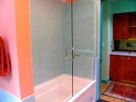 Bathtub surround with irridecent blue/green glass tile.