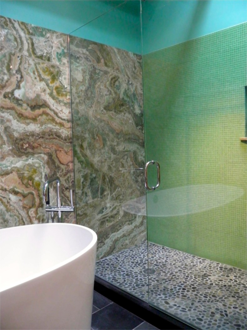 Master Bath walk-in shower with green glass tile on side wall. Green Onyx slab on back wall.