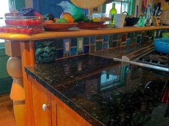 Black speckled granite counter on Cherry cabinets with a Pewabic tile backsplash.