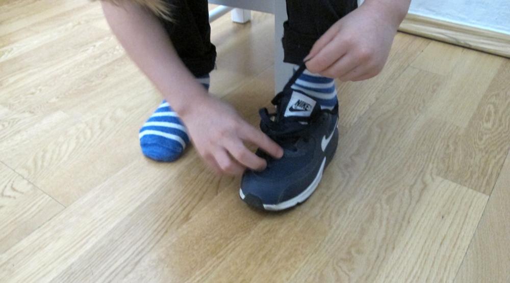 Junge bindet Turnschuhe Nike
