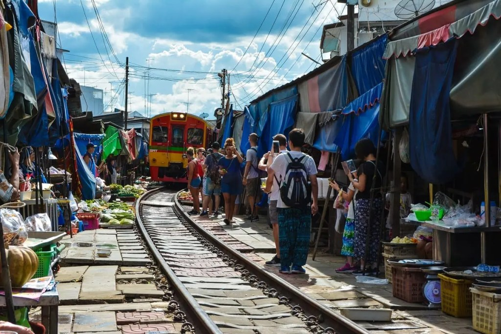 Tourists line up along the track to see the train pass through the market -  Samut, Thailand (source:unsplash)
