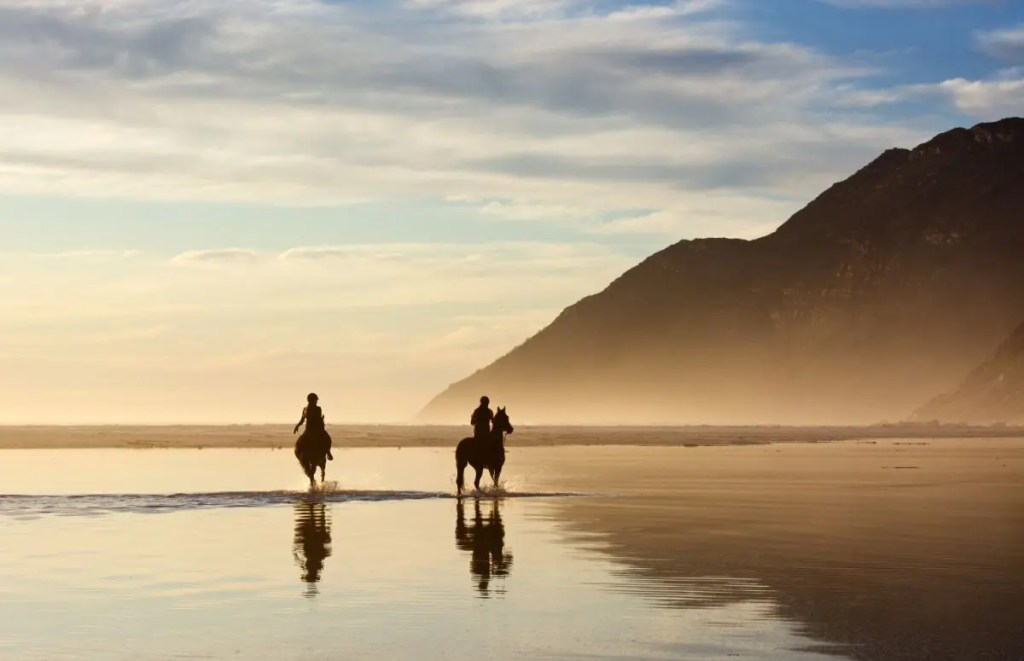 A Couple Rides on Horseback along Noordhoek Beach. Image: Shutterstock