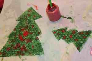 This Christmas tree print making activity is fun for toddlers (and kids of all ages). With simple materials and adorable results, your kids will make keepsakes you'll treasure for years to come. Get the instructions at TheSaltyMamas.com. #christmasart #christmasartfortoddlers #christmas #holidays #toddlers #artforkids #kidsart #toddlerart #christmastreeart