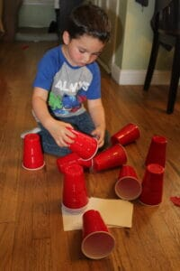 toddler knocking down a red solo cup tower