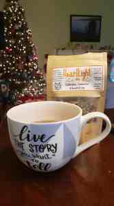 "a cup of tea in a cup that says ""live the story you want to tell,"" in front of a bag of loose tea called heartlight"