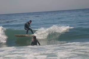 Sage Linden-Engle surfing Freesia Bauer watching