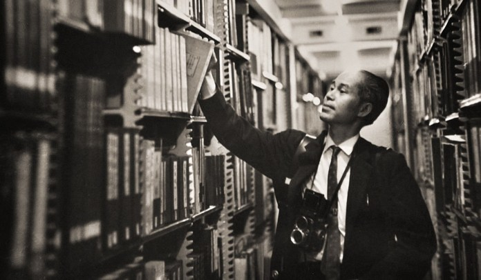 Black and white image of Kem Lee surrounded by tall library shelves, pulling a photo book out of the archives.