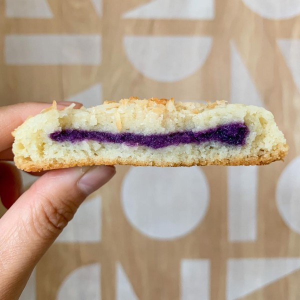 A thumb and forefinger hold up a white coconut cookie with purple ube halaya filling.