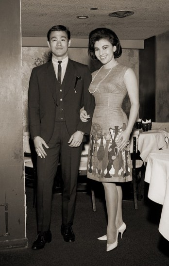 Sepia image of Bruce Lee standing with Diana Chang Chung-Wen in a theatre, dressed in formal attire.
