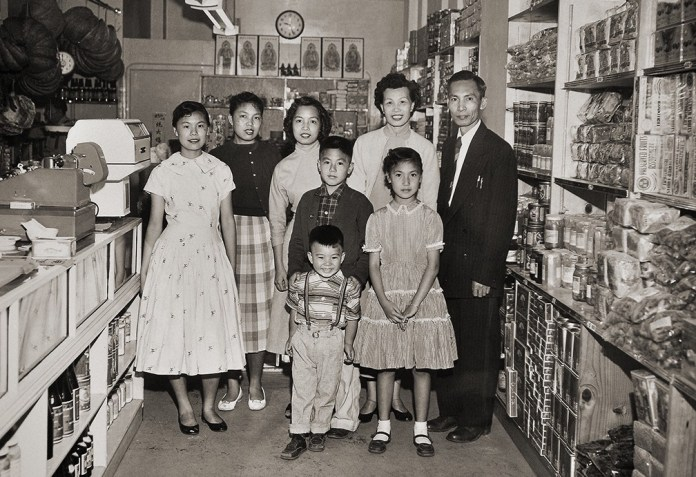 Sepia photo of family standing in a Chinatown shop.