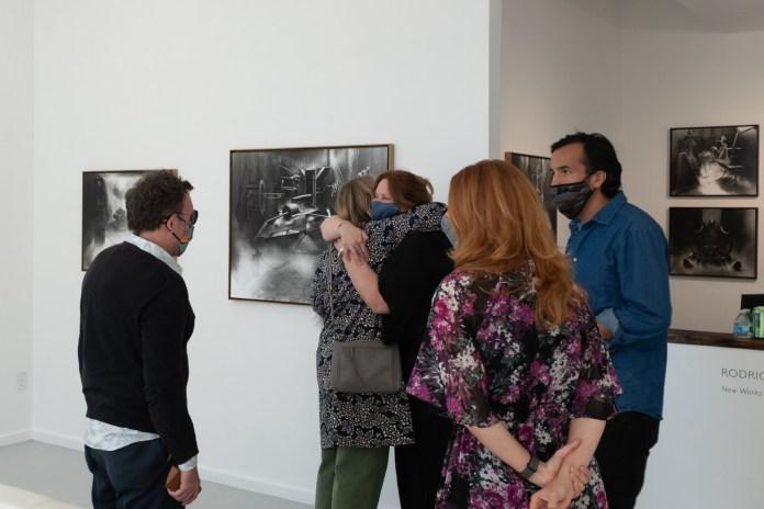 A masked group stands inside an art gallery. Two women hug.