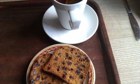Photo of two slices of fruitcake and a cup of tea