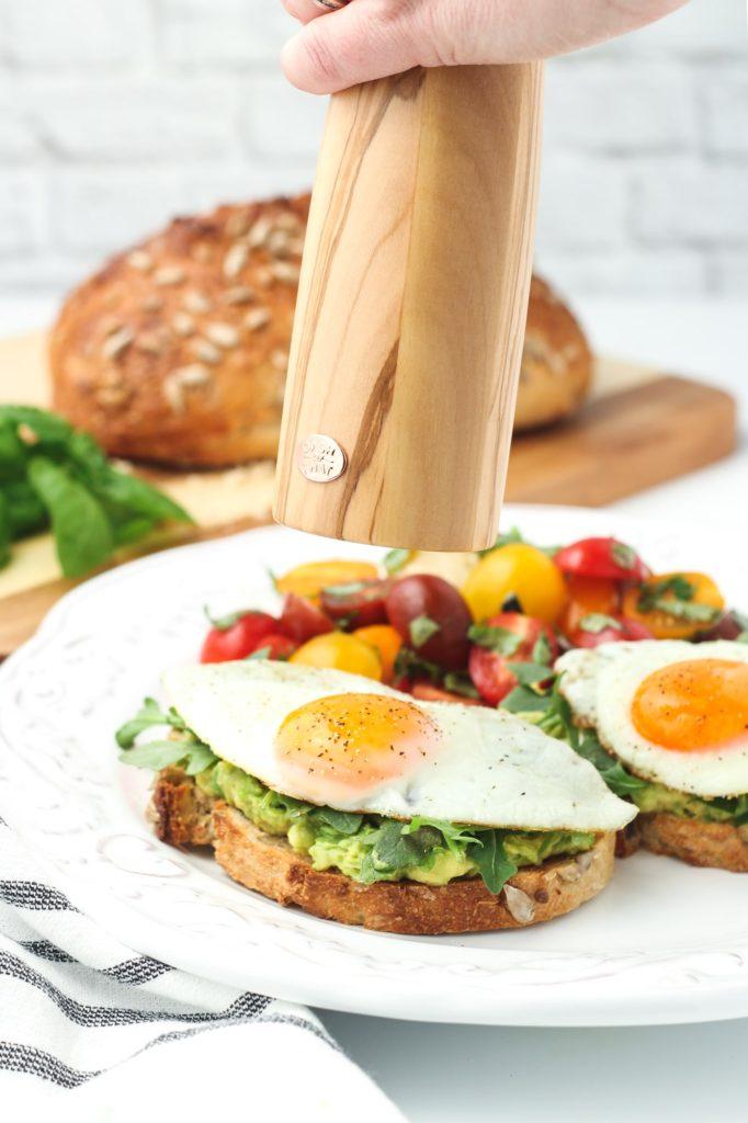 Grinding fresh black pepper over a sunny side egg on avocado toast