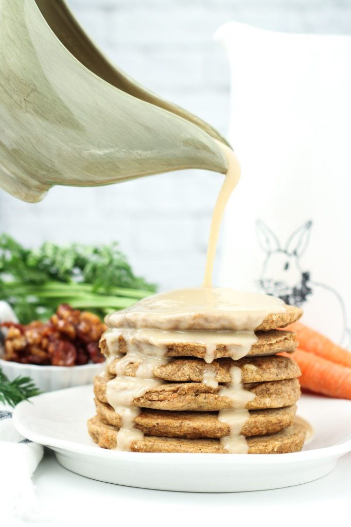 pouring cashew maple syrup over the carrot cake pancakes