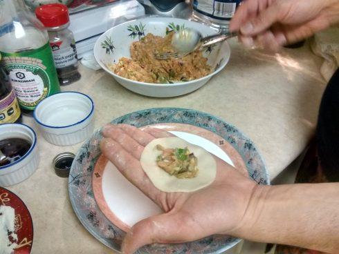dumpling wrapper in open hand with meat inside