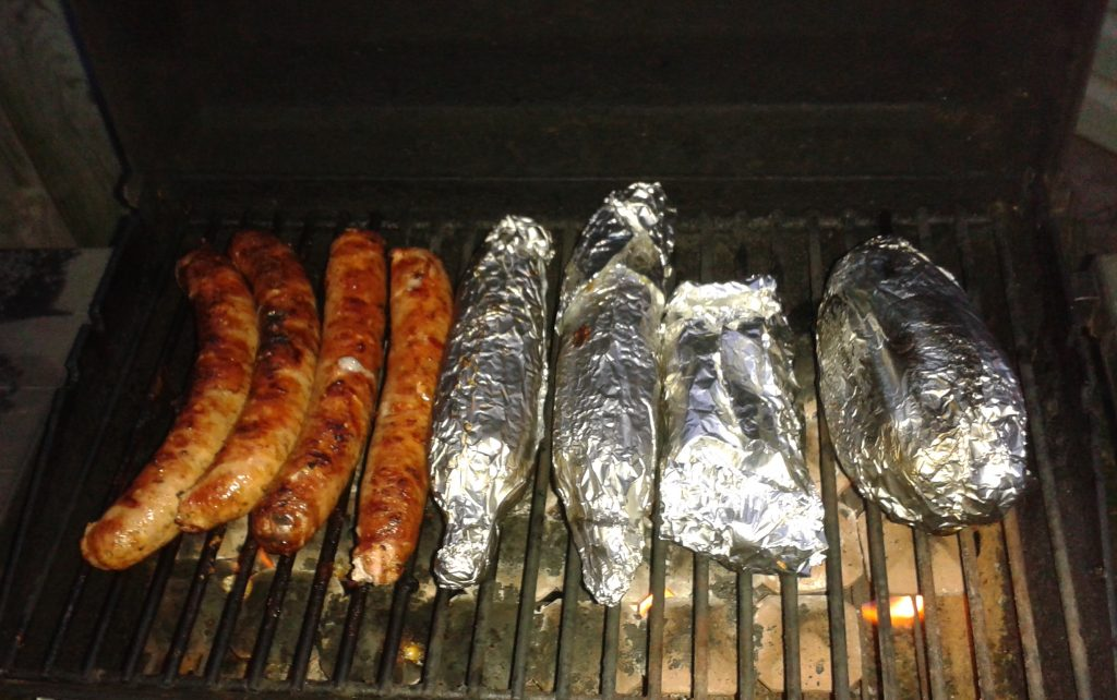 Sausages and baked potatoes on the BBQ