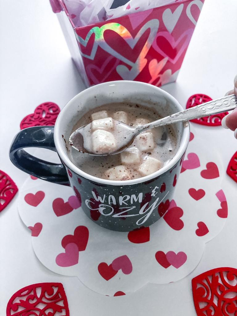 Hot cup of milk with chocolate bomb with marshmallows