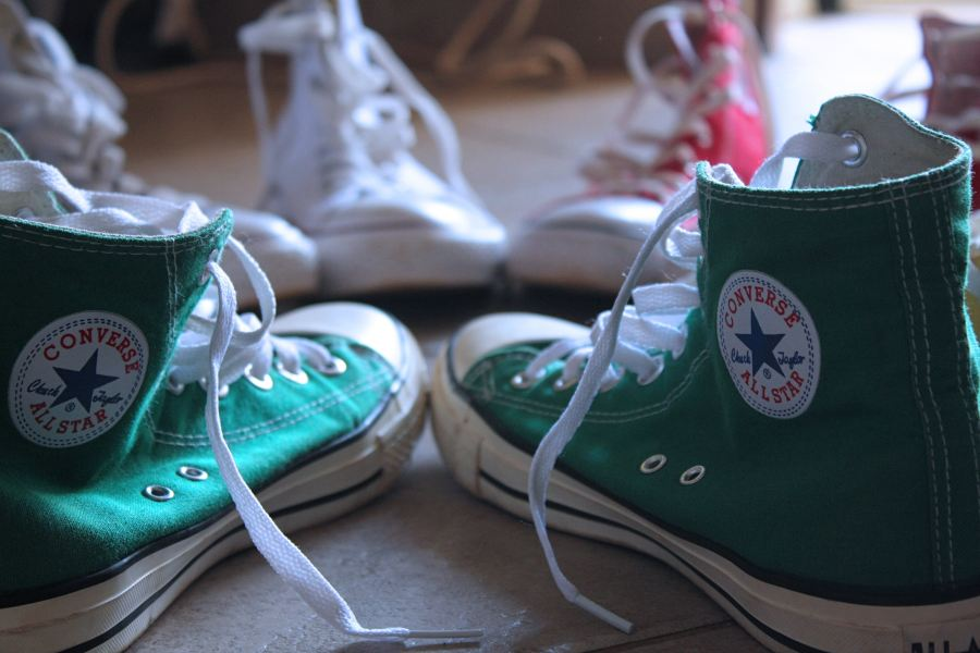 Photo by Andrew Itaga on Unsplash green chuck taylor converse shoes with white shoes and red shoes in the background