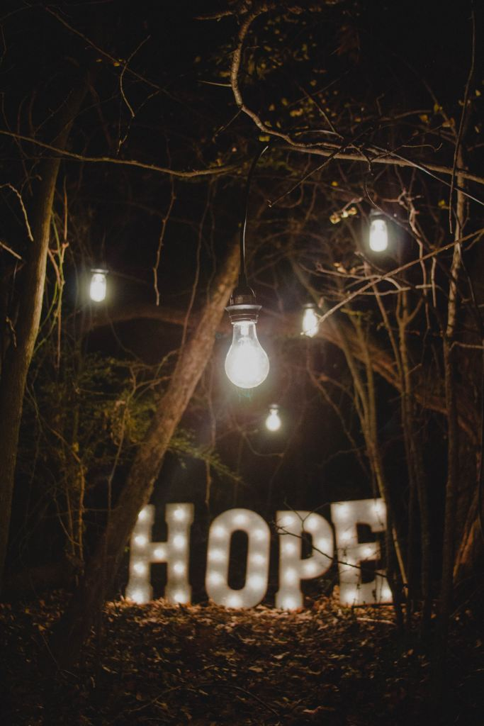 Photo by Ron Smith on Unsplash lighted hope letters outside in the dark in the forest with light bulbs