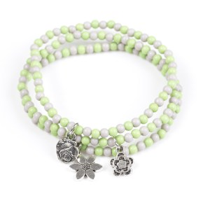Dainty green and gray beads are threaded along stretchy elastic bands, creating colorful layers across the wrist. Brushed in an antiqued shimmer, dainty floral charms swing from the wrist for a seasonal finish. Sold as one set of three bracelets.
