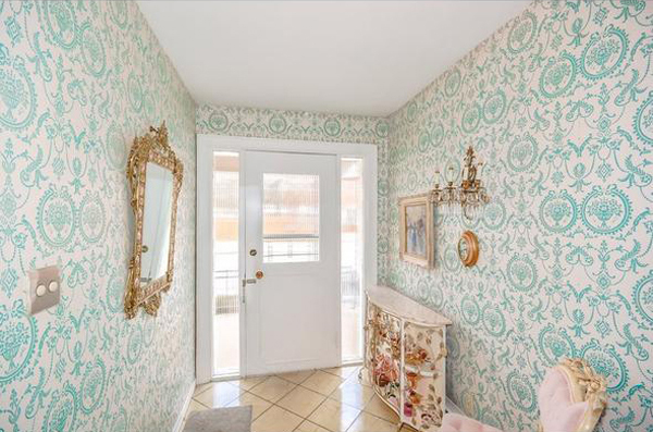 Hallway with gold mirrors and light blue and white baroque wallpaper.