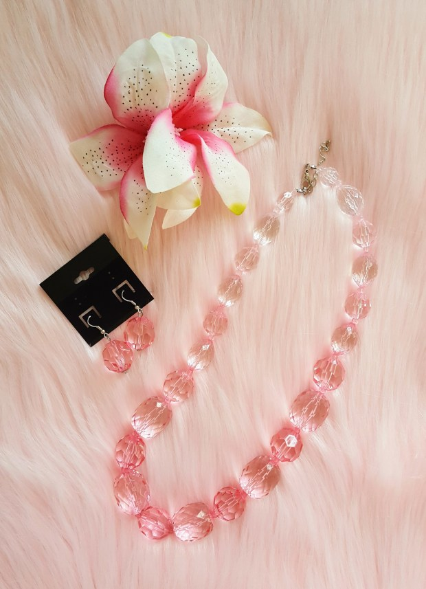 Pink necklace, earrings, and hair flower on a pink background