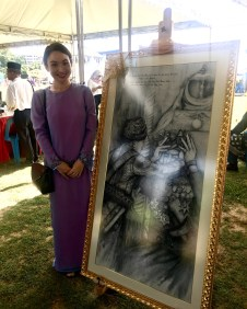 Artist Hui Fong Ng poses with a Chinese ink portrait of His Majesty. Photo: Ain Bandial/The Scoop