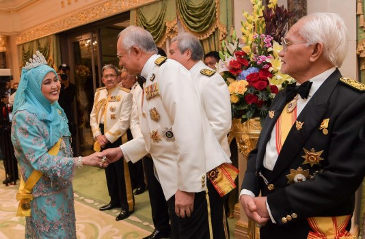 Her Majesty the Raja Isteri greets Malaysian PM Najib Razak (C), while the YDP of Sarawak Taib Mahmud looks on. Photo: Infofoto