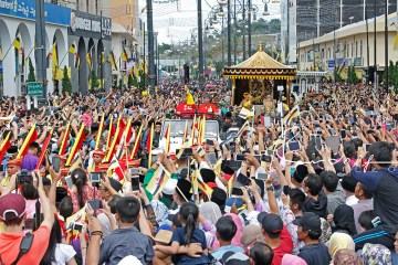 His Majesty waves to well- wishers during the procession as part of the Golden Jubilee celebrations in Bandar Seri Begawan. Photo: Rudolf Portillo