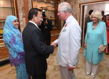 His Majesty greets Prince Charles as he arrives at Istana Nurul Iman, while HM the Raja Isteri and the Duchess of Cornwall look on. Photo: Infofoto