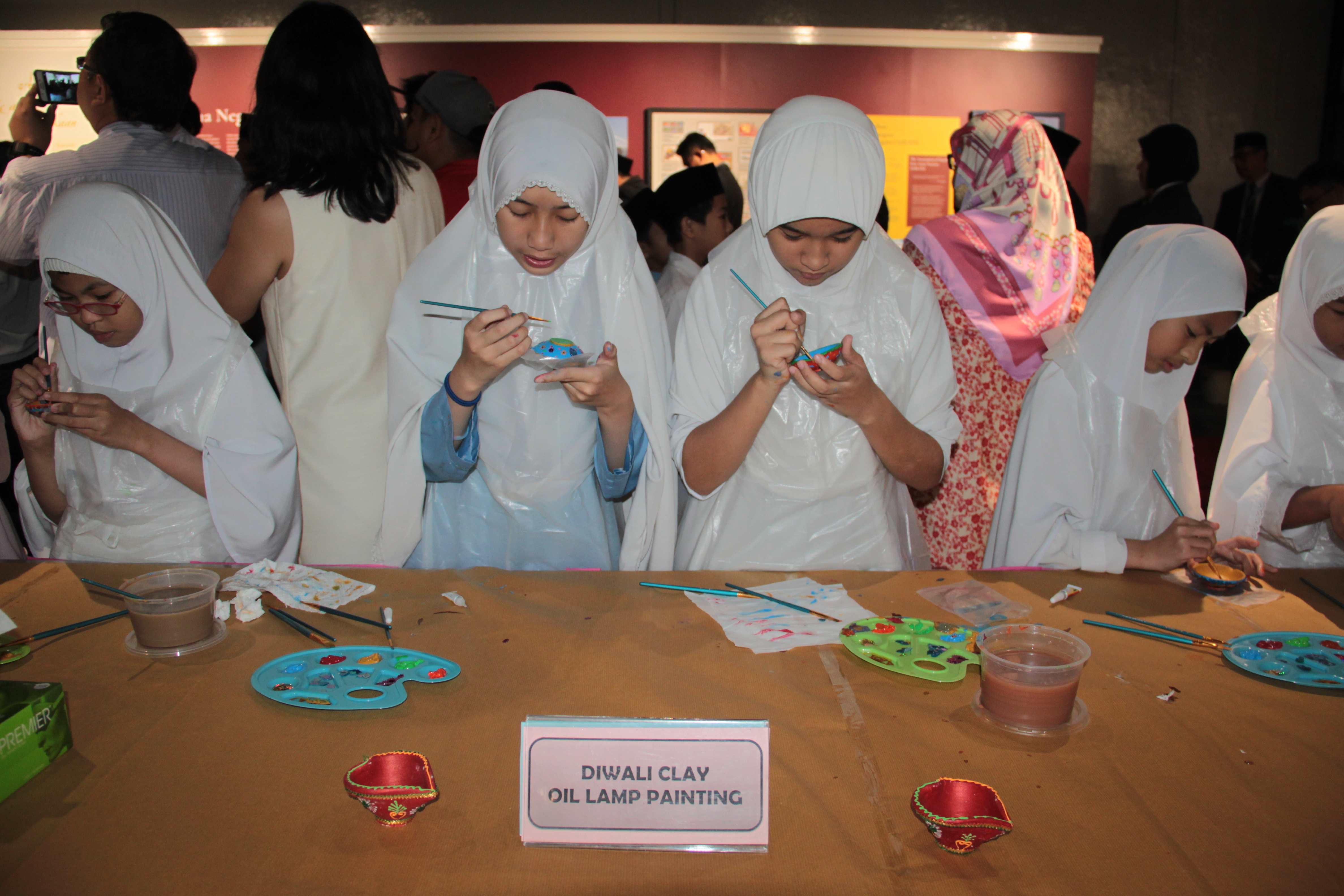Students painting Diwali clay oil lamp as part of the activities at 'Abode of Peace & the Lion City: A Brunei-Singapore Exhibition' at Royal Wharf in the capital. Photo: Rasidah Hj Abu Bakar