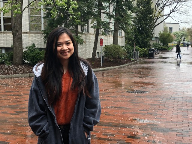 Nesanne Mae Tam, a college sophomore, stands on the brick walkway outside Northeastern's library. She has long black hair and is wearing a grey sweatshirt.