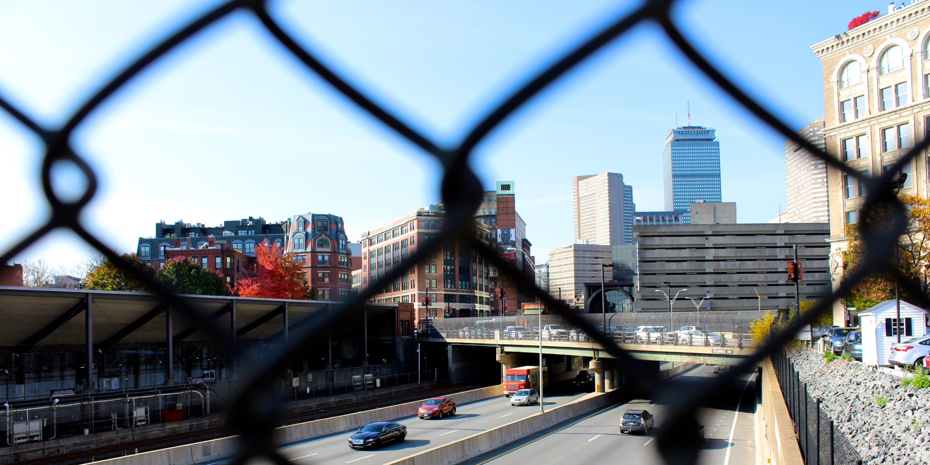 this photo shows boston highway and skyline visible through a chain link fence