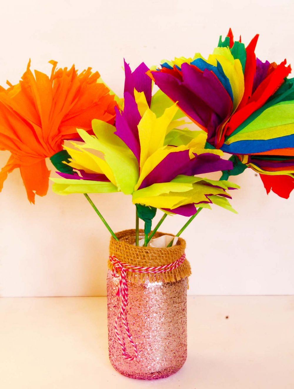 Easy tissue paper flowers made with crepe paper in various colors