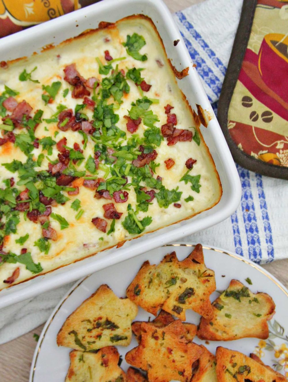 Bread chips next to a casserole of hot cheese dip with bacon and parsley