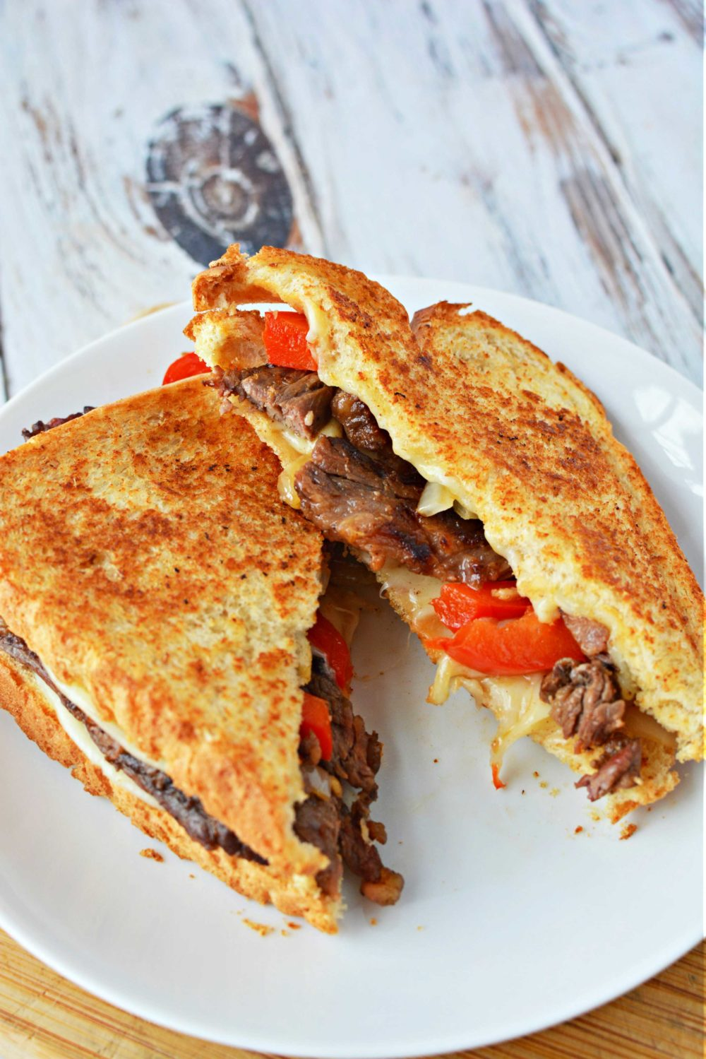 Philly cheesesteak grilled cheese with onion, red bell peppers, hot sauce and provolone cheese