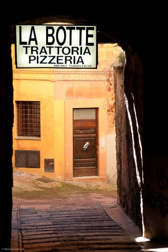 Splashes of light along a dark wall bordering a sidewalk in Perugia.