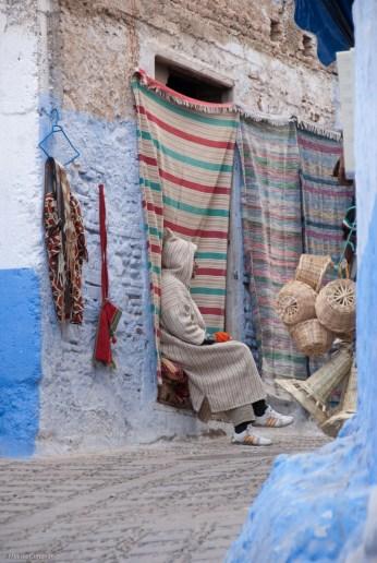 A shopkeeper smokes outside his shop.
