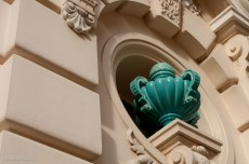 A gracefully-curved green urn in an outdoor niche.