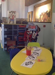 A picture of the children's area, with art cart and dressing up clothes