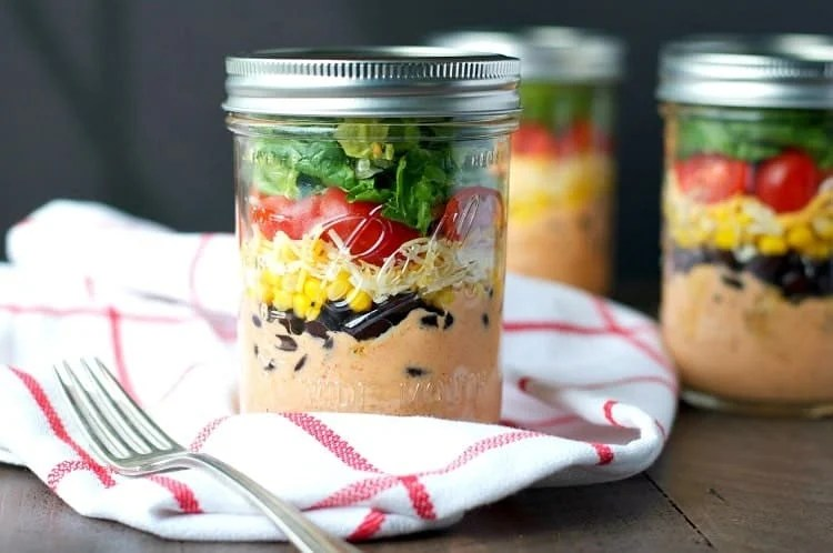 With only about 10 minutes of prep (and no cooking!) you can prepare these healthy Chicken Taco Mason Jar Salads to keep in your refrigerator for a busy week ahead! Whether you serve them as portable lunches or last-minute dinners, these salads are loaded with fresh veggies, plenty of cheese, and almost 40 grams of protein for a nutritious and satisfying meal at any time of day!