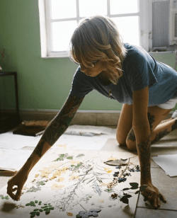 The artist kneeling on the ground putting some finishing touches on her work which is laid out on the floor