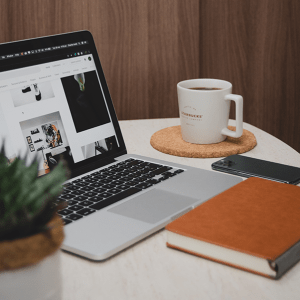 a laptop, mug of coffee, phone, book and a succulent plant on a white table