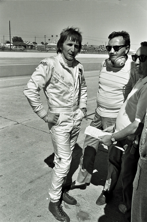Derek Bell seen talking to legendary sports announcer Chris Economackie at the 1971 Sebring 12 Hour Race. Bell co-drove with Jo Siffert in a Porsche 917K. They finished 5th with Bell getting 1st in the Rod Stewart lookalike contest..