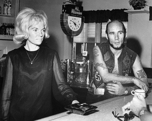 """Case involving members of """"Outlaws"""" motorcycle club, who are accused of nailing a female member of their club to a tree for holding out $10.  Mrs. Bertha (Kitty) Randall and tattooed biker Donald """"Deke"""" Tanner inside her bar  --West Palm Beach, FL 1967."""